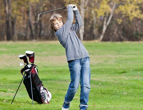 Young golfer playing a shot from the fairway. Blonde caucasian kid. Autumn Season.